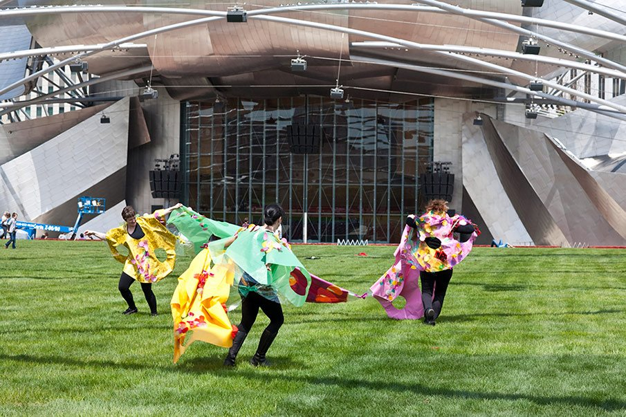 Three people run in colorful capes at Chicago's Millennium Park
