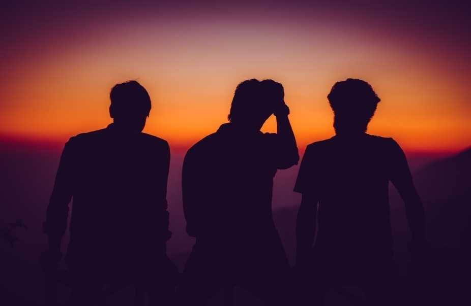 Three male silhouettes against sunset.